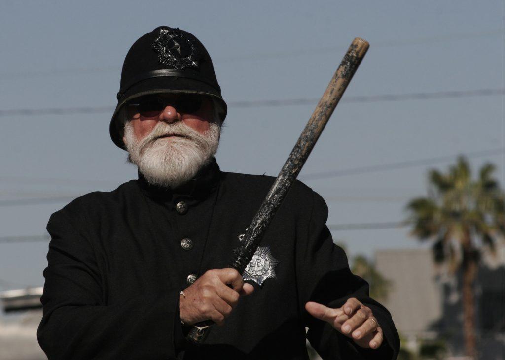Agent de police qui lève sa matraque
